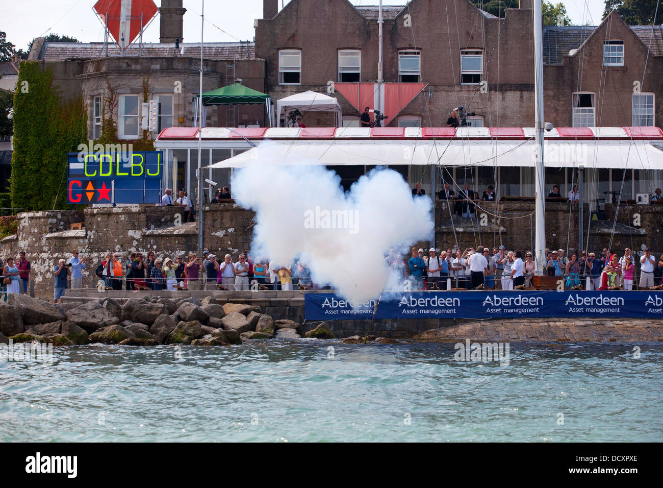 Cannon Smoke blast Royal Yacht Squadron Cowes Week spectators yacht racing finish start Aberdeen Asset Management - Stock Image