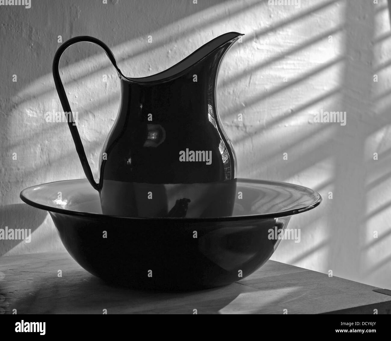 A Black And White Picture Of A Jug And Bowl In A Bathroom Stock