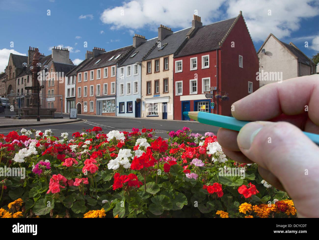 Digitally Enhanced Image Of Hand Holding Pencil Against Town; Jedburgh, Scottish Borders, Scotland - Stock Image