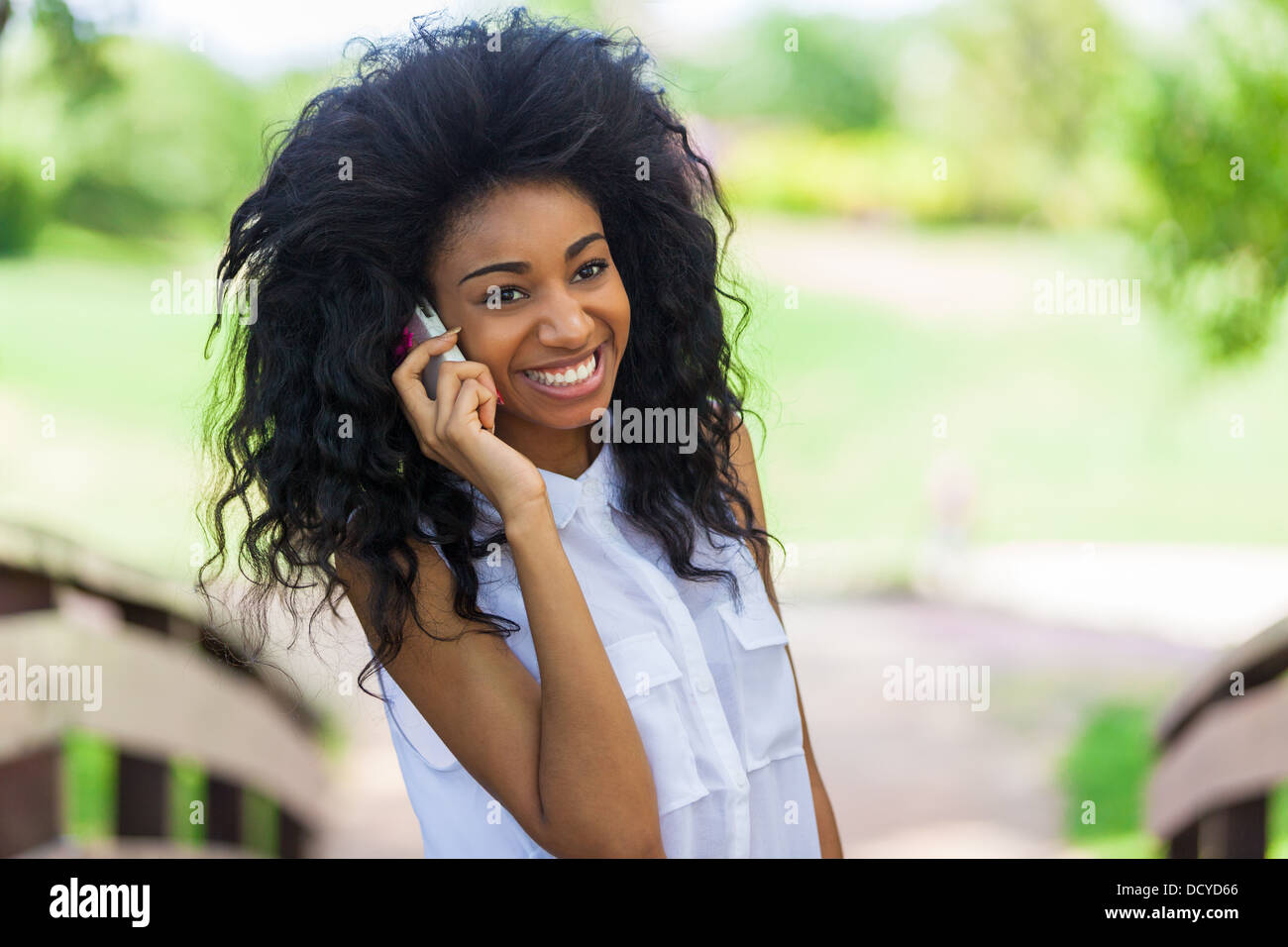 Smiling teenage black girl using a mobile phone - African people - Stock Image