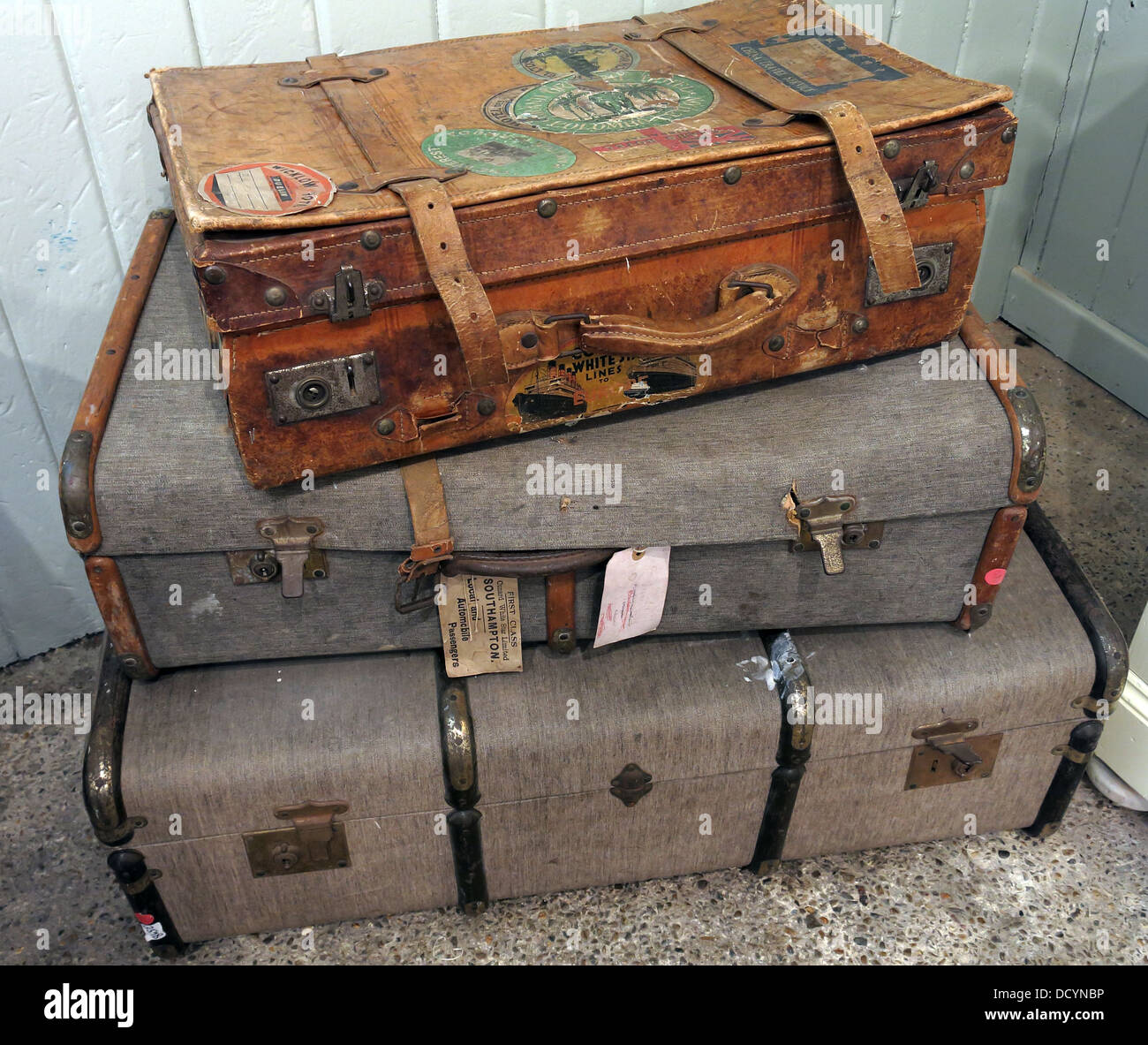 3 Old suitcases filed up with luggage labels - Stock Image
