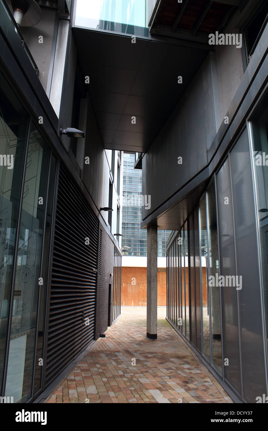 A passageway between two modern buildings with dark contrasts - Stock Image