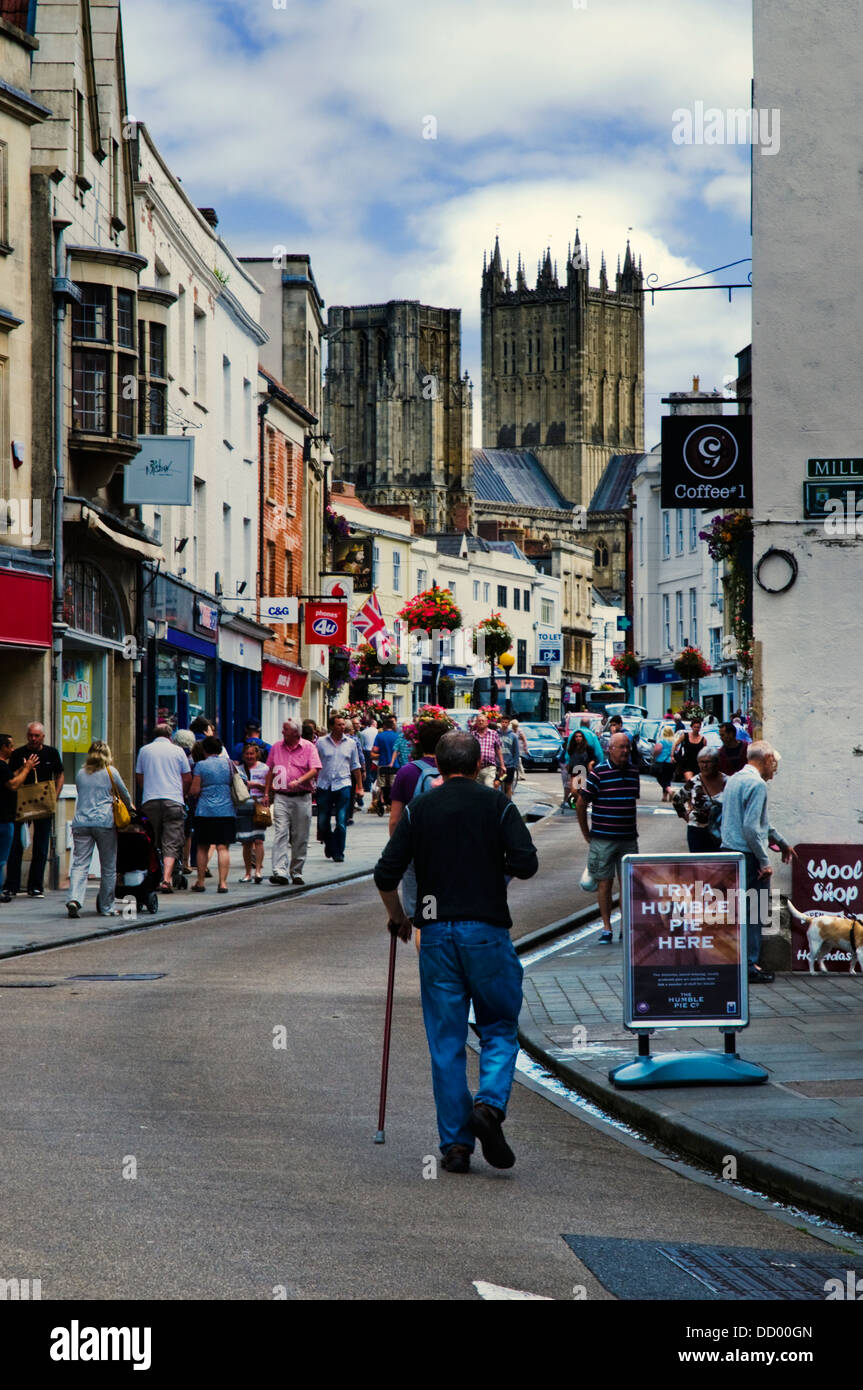 A man with a walking stick walks up a street in Wells, the smallest city in England, towards the cathedral. - Stock Image