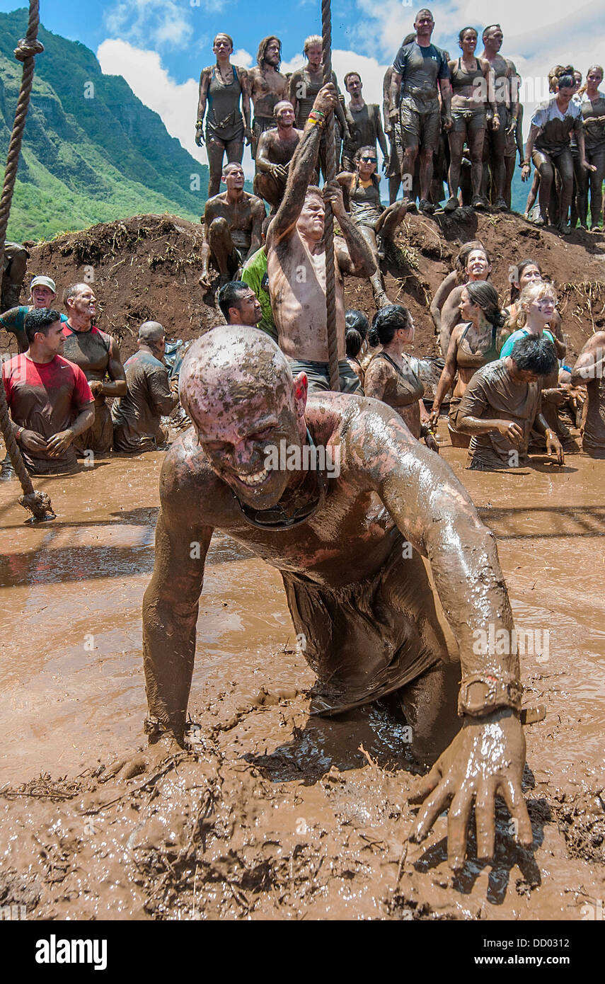 US Military service members crawl through the mud as they join civilians as they participate in Hawaii's first - Stock Image