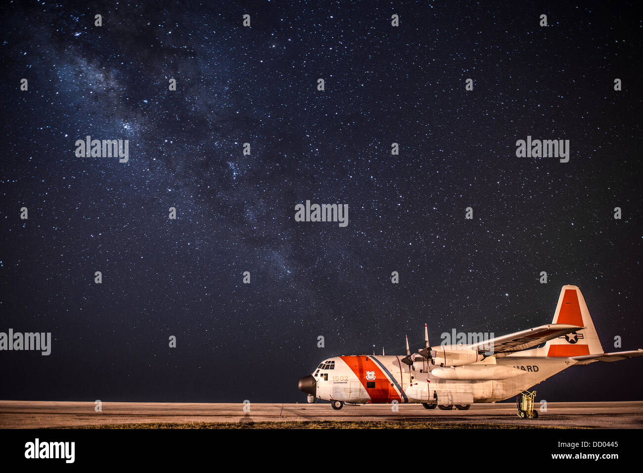 A US Coast Guard C-130 Hercules aircraft assigned to Coast Guard Air Station Clearwater sits parked on the tarmac - Stock Image