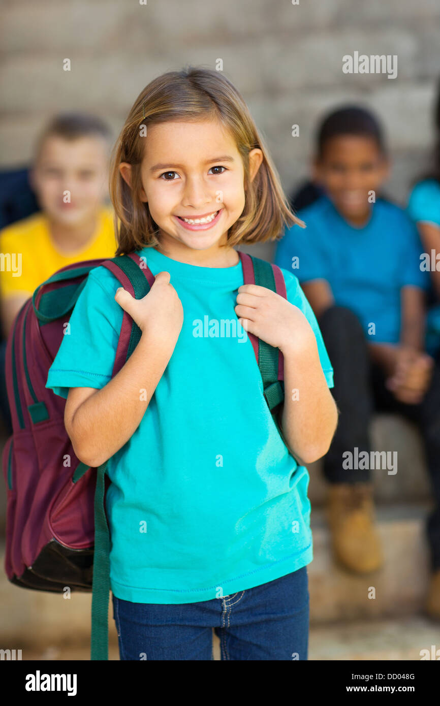 cute elementary schoolgirl carrying schoolbag in front of classmates - Stock Image