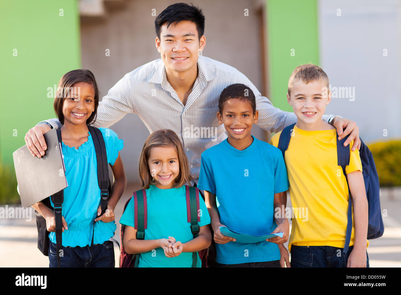 four elementary school students and teacher on campus - Stock Image