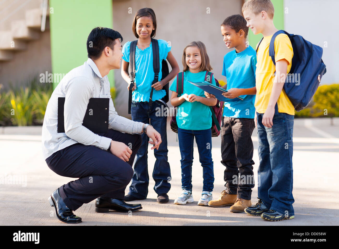 cute elementary pupils outside classroom talking to teacher - Stock Image