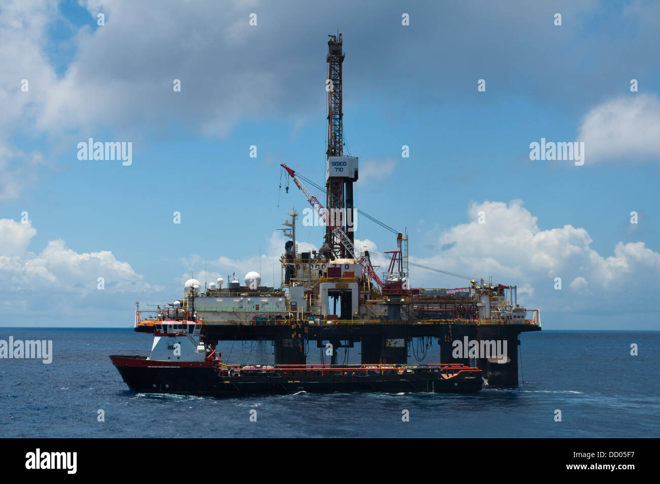 SS 43 oil drilling rig working for Petrobras offshore Campos basin, Rio de Janeiro, Brazil, with supply vessel along - Stock Image