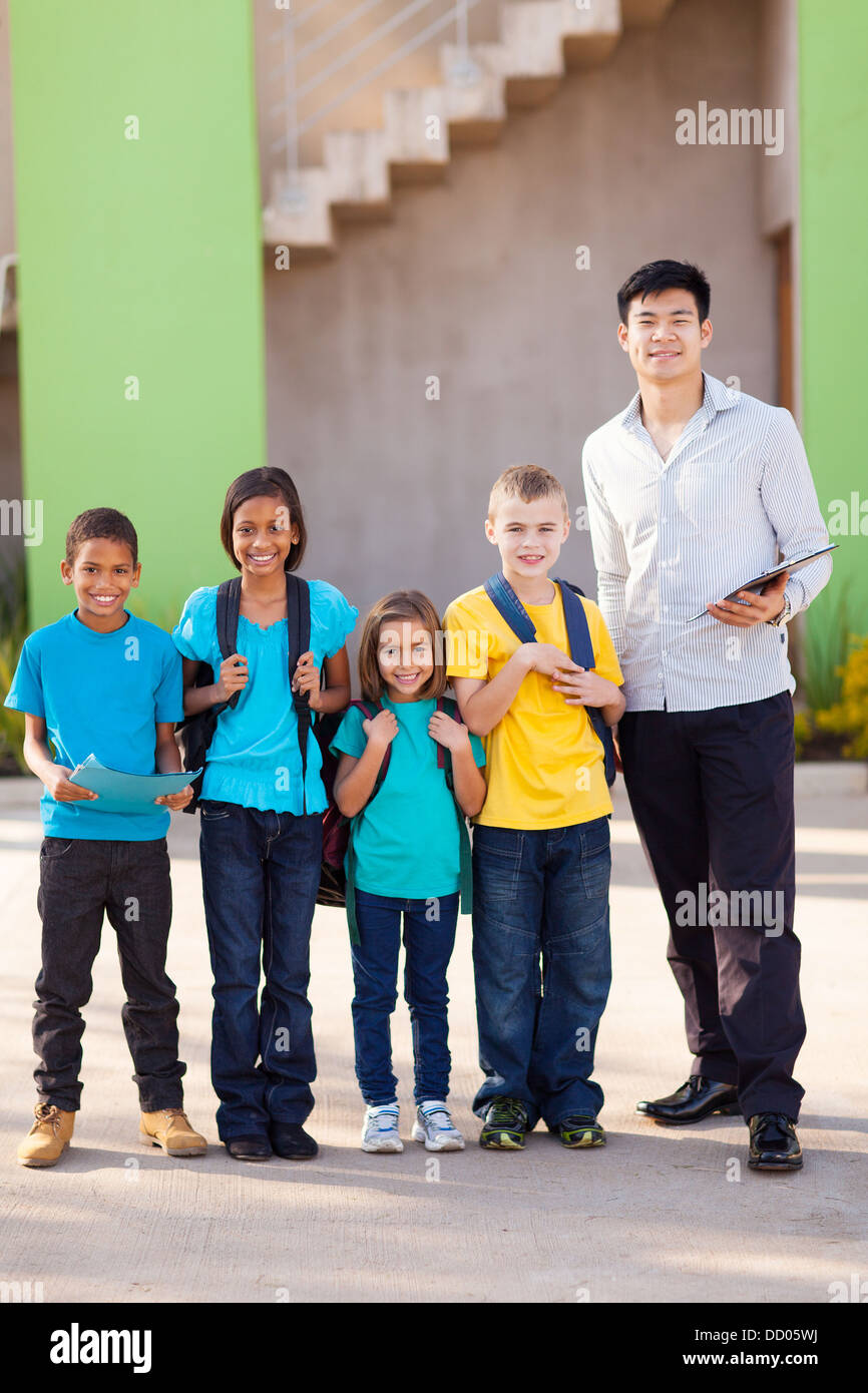 handsome teacher and elementary school students on campus - Stock Image