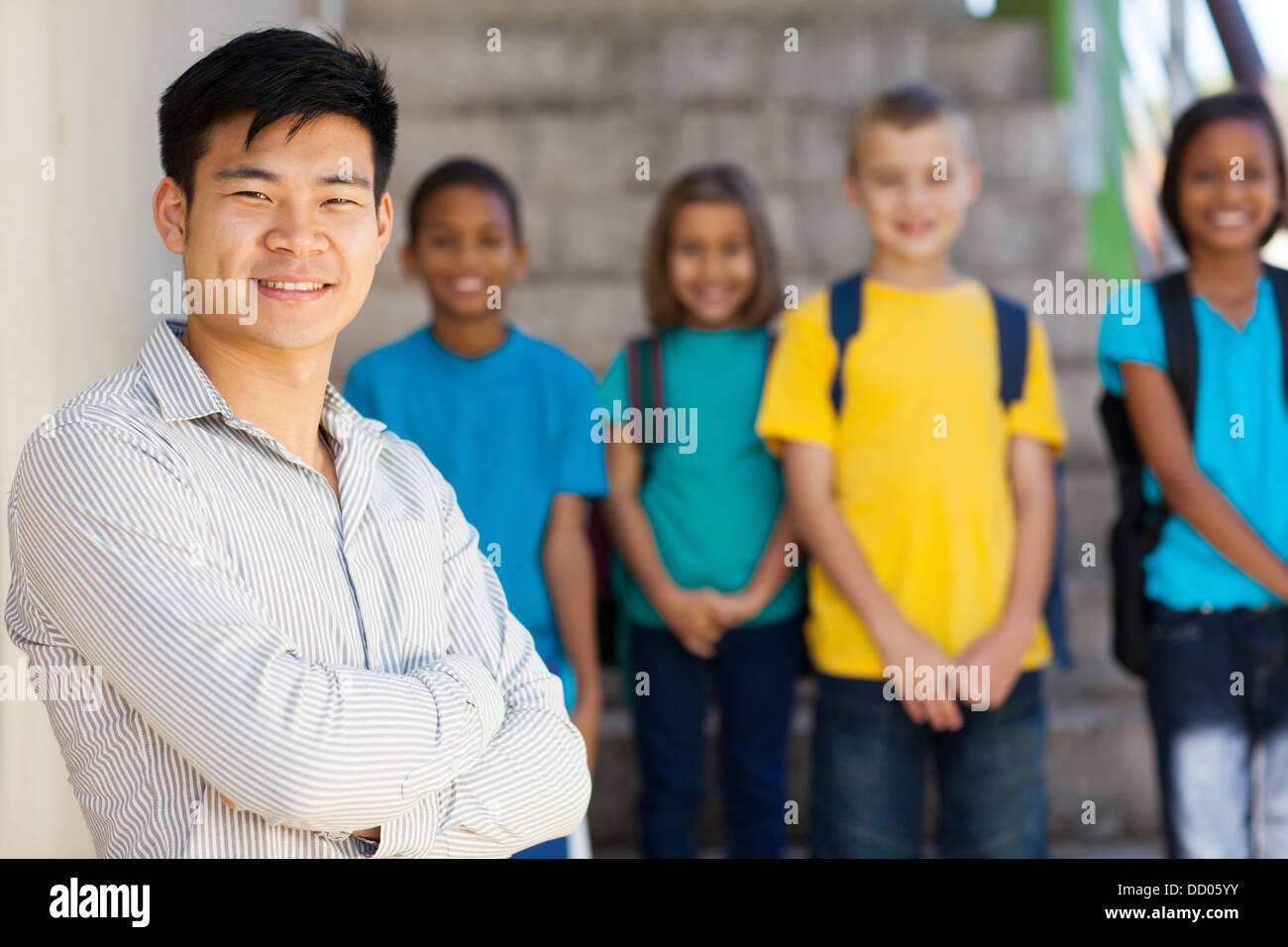 handsome male elementary educator with students on background - Stock Image