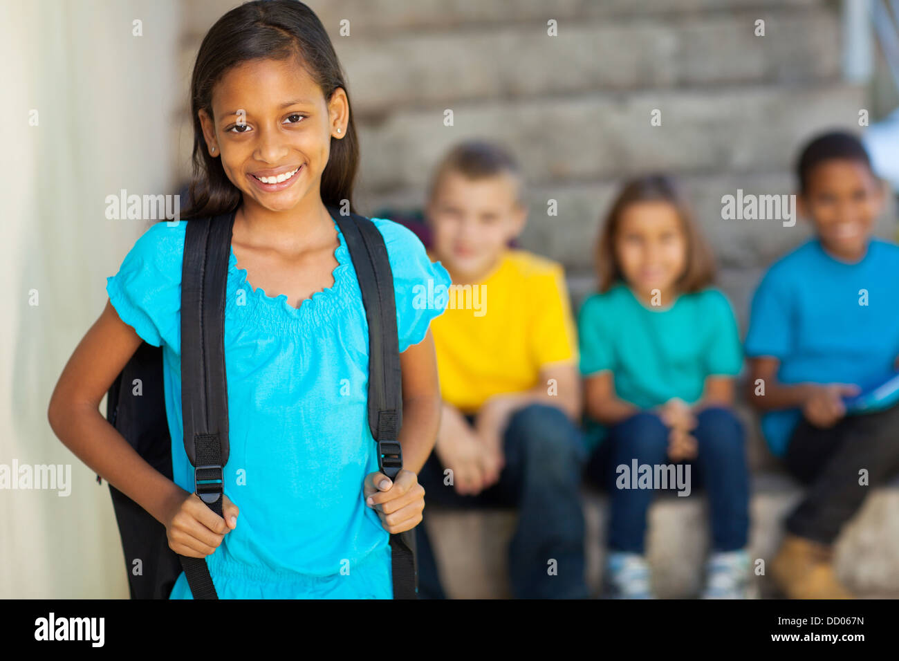 portrait of beautiful elementary school girl with schoolmates on background Stock Photo