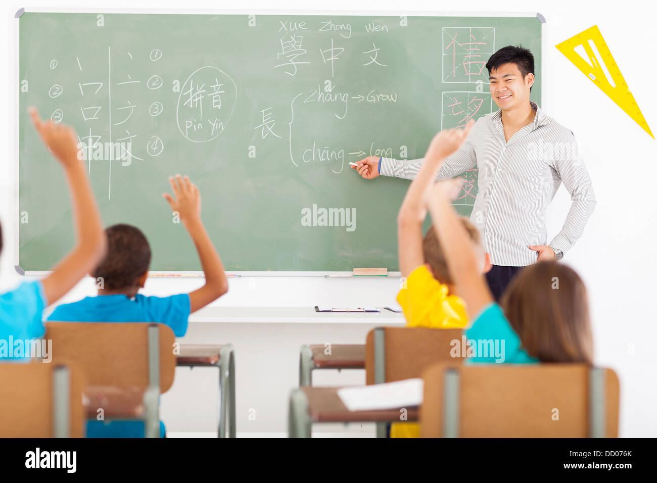 smiling educator teaching chinese language to group of primary kids - Stock Image