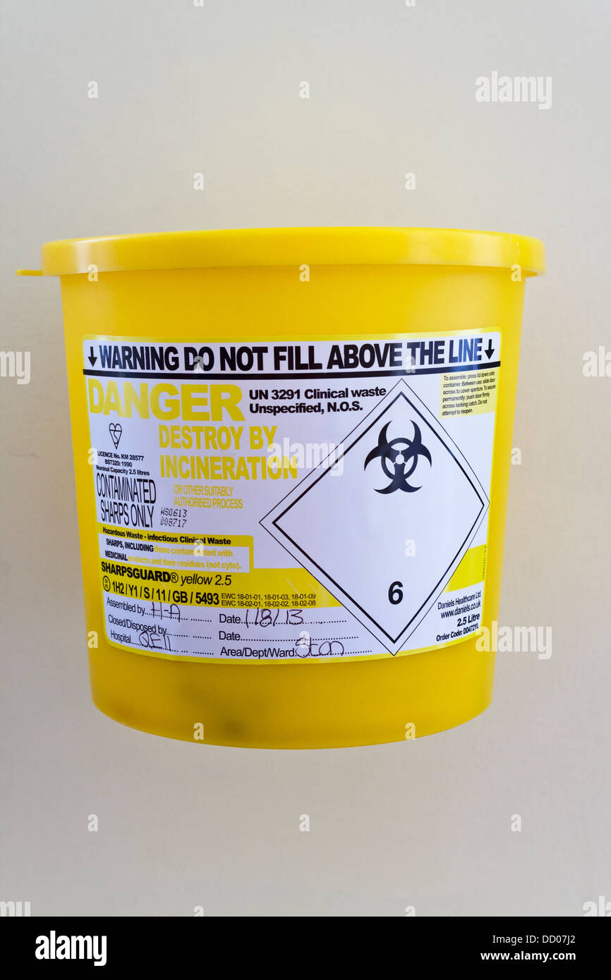 Sharps contminates bin for disposal of used needles on a hospital ward. - Stock Image