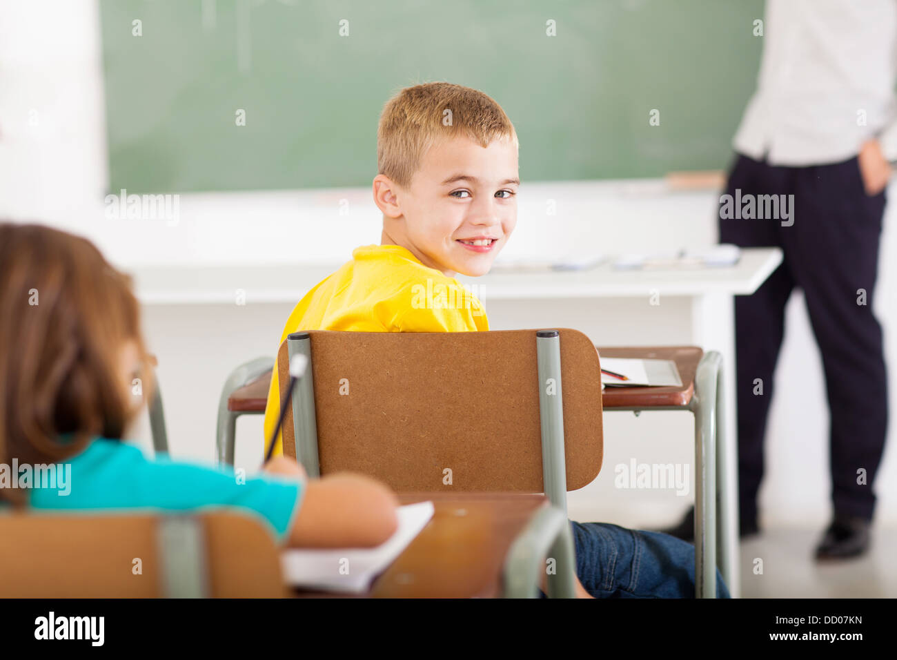 cute primary school student looking back in classroom - Stock Image