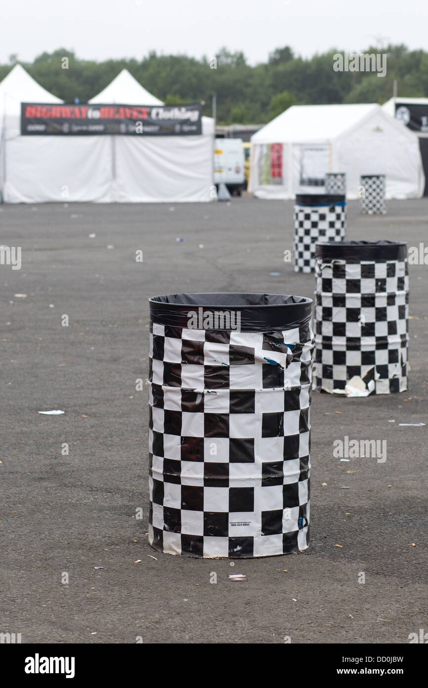 Empty Trash Cans in a line at a Festival with Tents in Background - Stock Image
