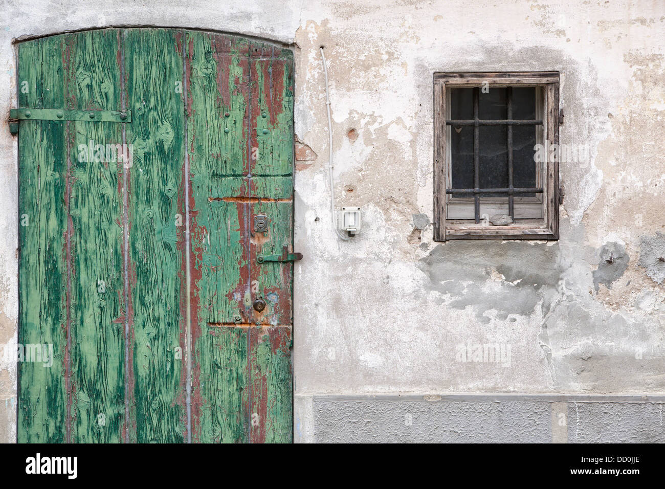 Fresh Detail of old stucco house with crumbling facade, green wooden  GQ39