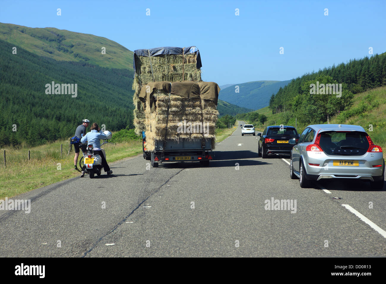 Slow moving vehicle, cyclist and motorcyclist in a lay-by allowing faster moving cars to overtake on the A83 in - Stock Image