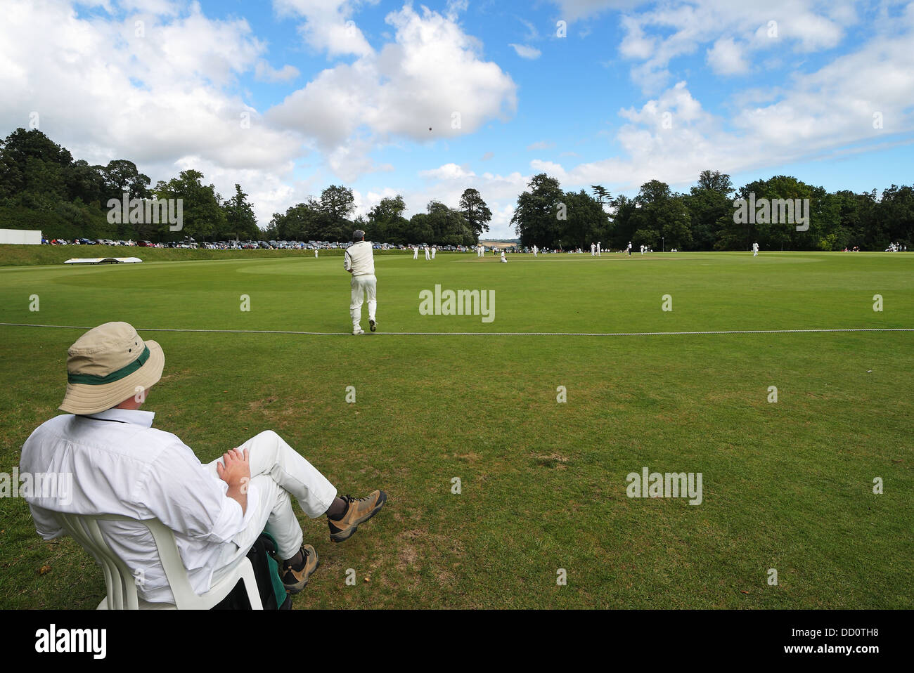 Batsman in action at an English Cricket match with spectator watching - Stock Image