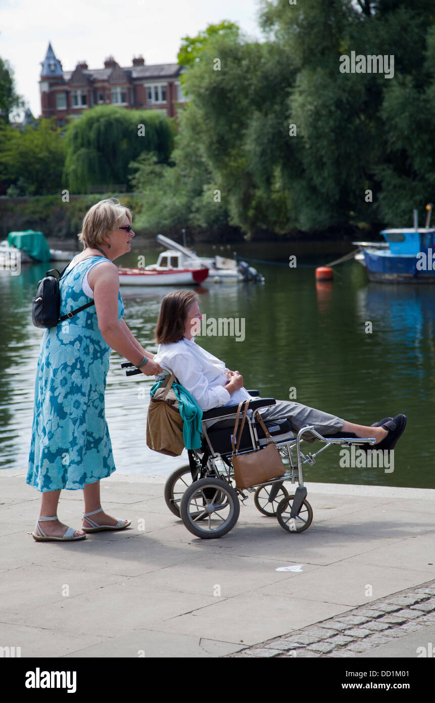 Woman in Wheelchair with 'Carer' on Richmond Riverside Towpath - TW9 - London UK - Stock Image