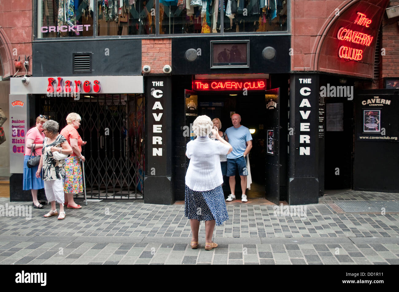 Elderly lady taking a photo at The Cavern Club, Liverpool, UK - Stock Image