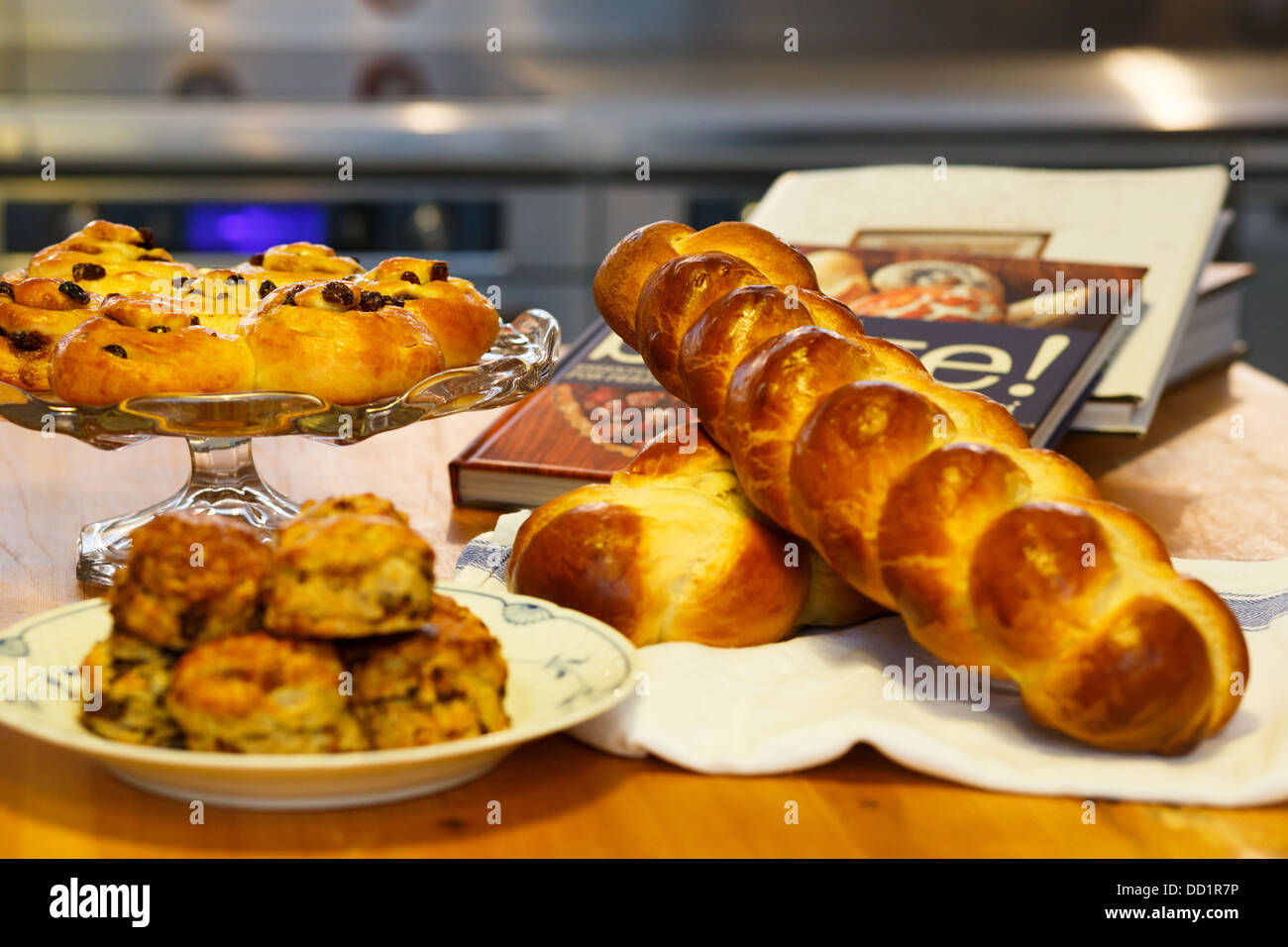 Mouth watering assortment of bakery items neatly arranged along with recipe books. - Stock Image