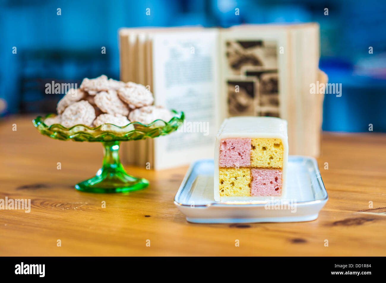 Yummy sponge cake and cookies for you. Enjoy them. Baking book in the background. Stock Photo