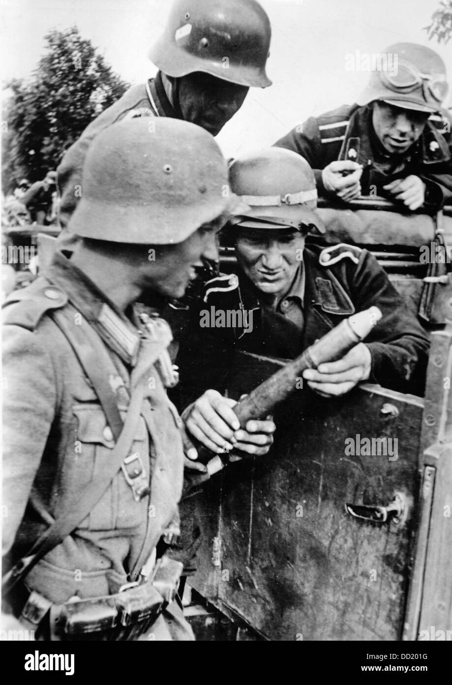 The image from the Nazi Propaganda! shows German members of an antitank unit examining grenades from a captured Stock Photo
