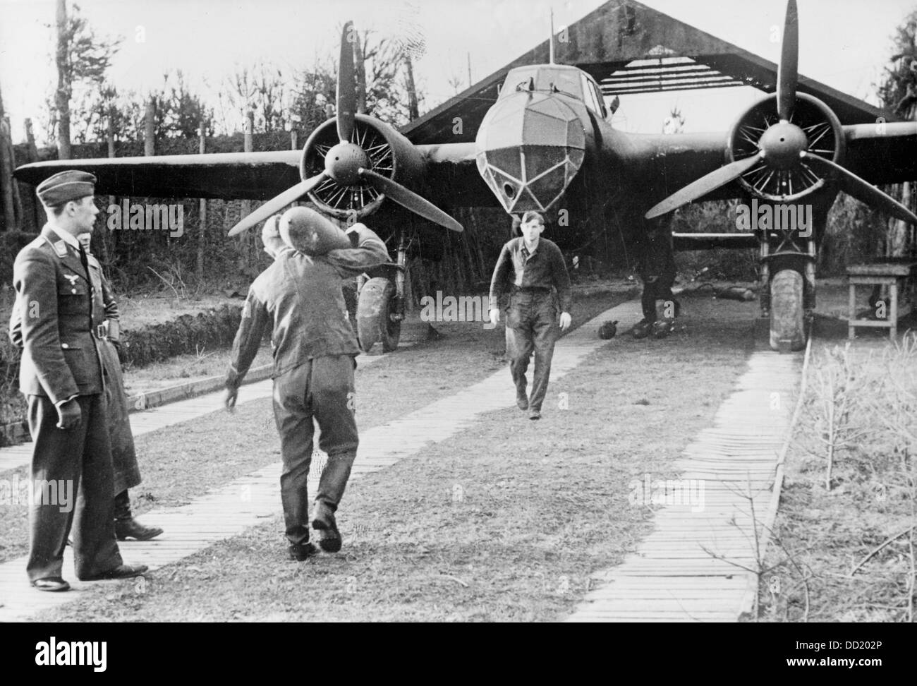 The image from the Nazi Propaganda! shows groundcrew members loading a plane with bombs for the next air raid of Stock Photo