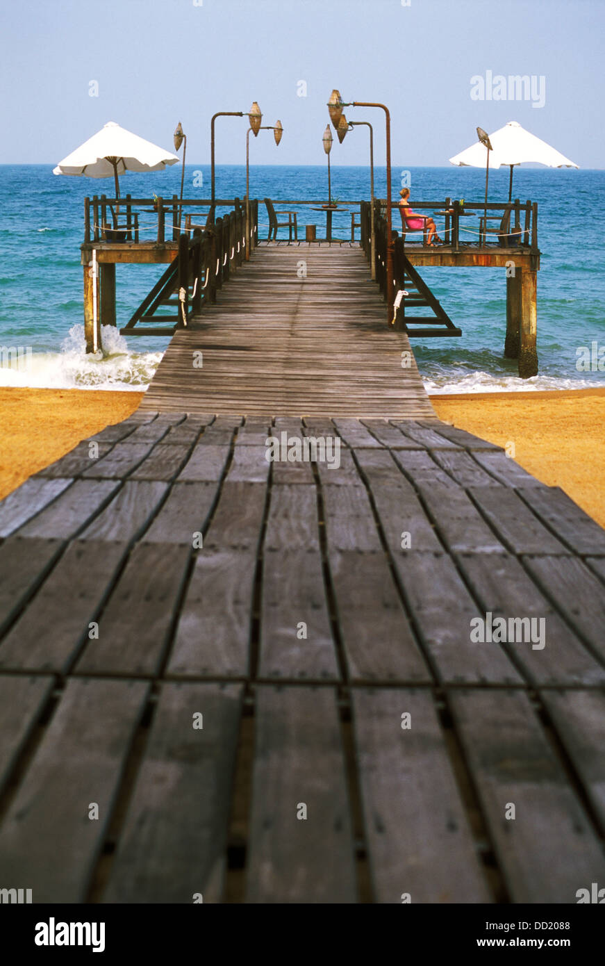 A pontoon in Nha Trang on the South China Sea. A lone women is sitting admiring the setting. - Stock Image