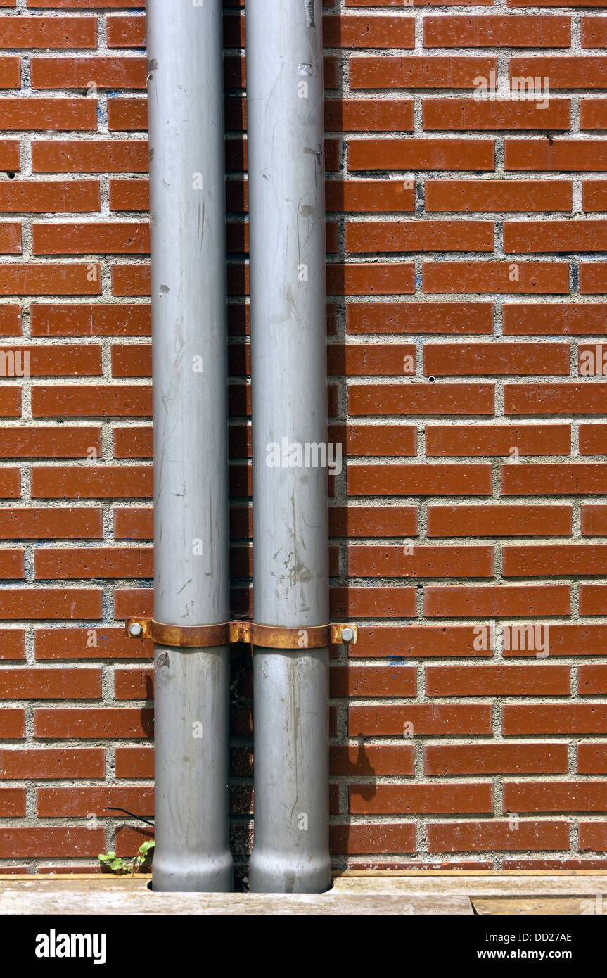drainpipe on a wall with bricks - Stock Image