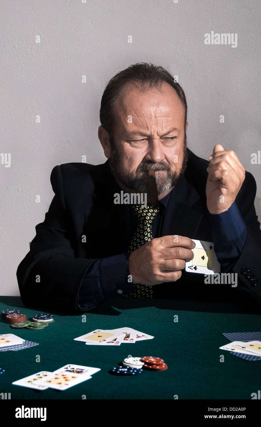 Man cheating at a game of poker. He puts an ace up his sleeve - Stock Image