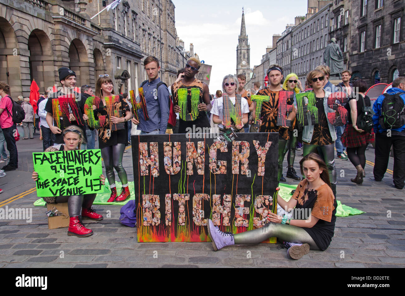 Performers promoting their play 'Facehunters' on the High Street in Edinburgh. - Stock Image
