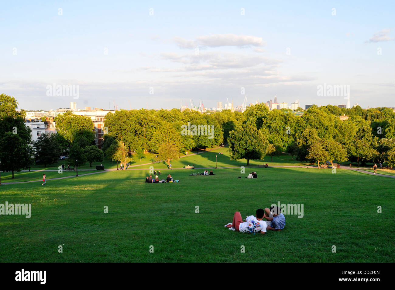 People relax in Primrose Hill during the hot weather, London, UK - Stock Image