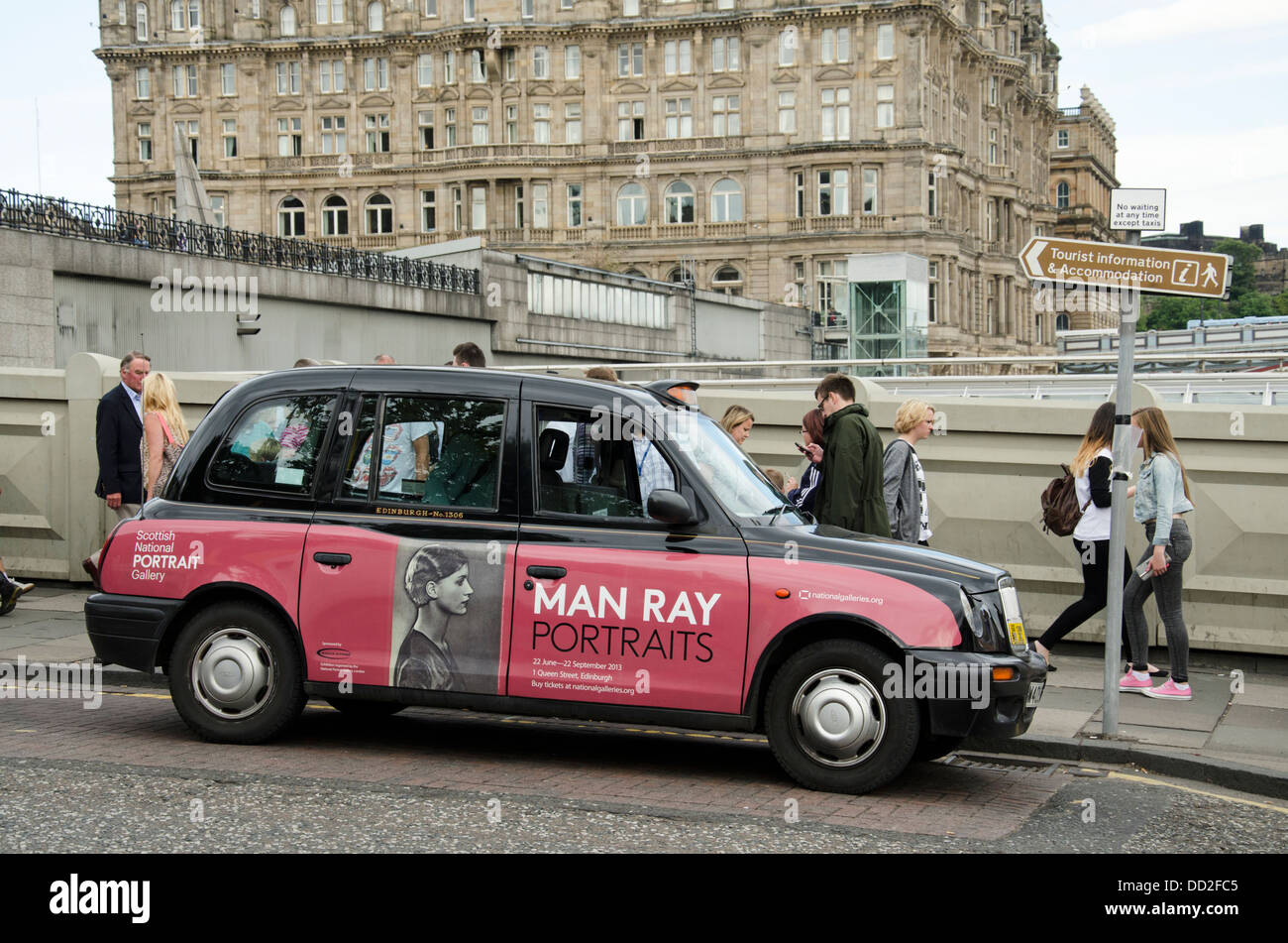 A taxi on Waverley Bridge with an advertisement for an Exhibition of Man Ray Portraits in the Scottish National - Stock Image