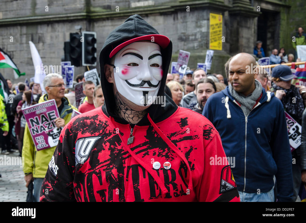 Anti-fascist protester wearing an Anonymous mask in Edinburgh's Old Town. - Stock Image