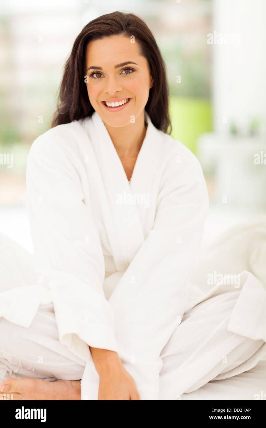 elegant young woman wearing nightwear sitting on bed - Stock Image