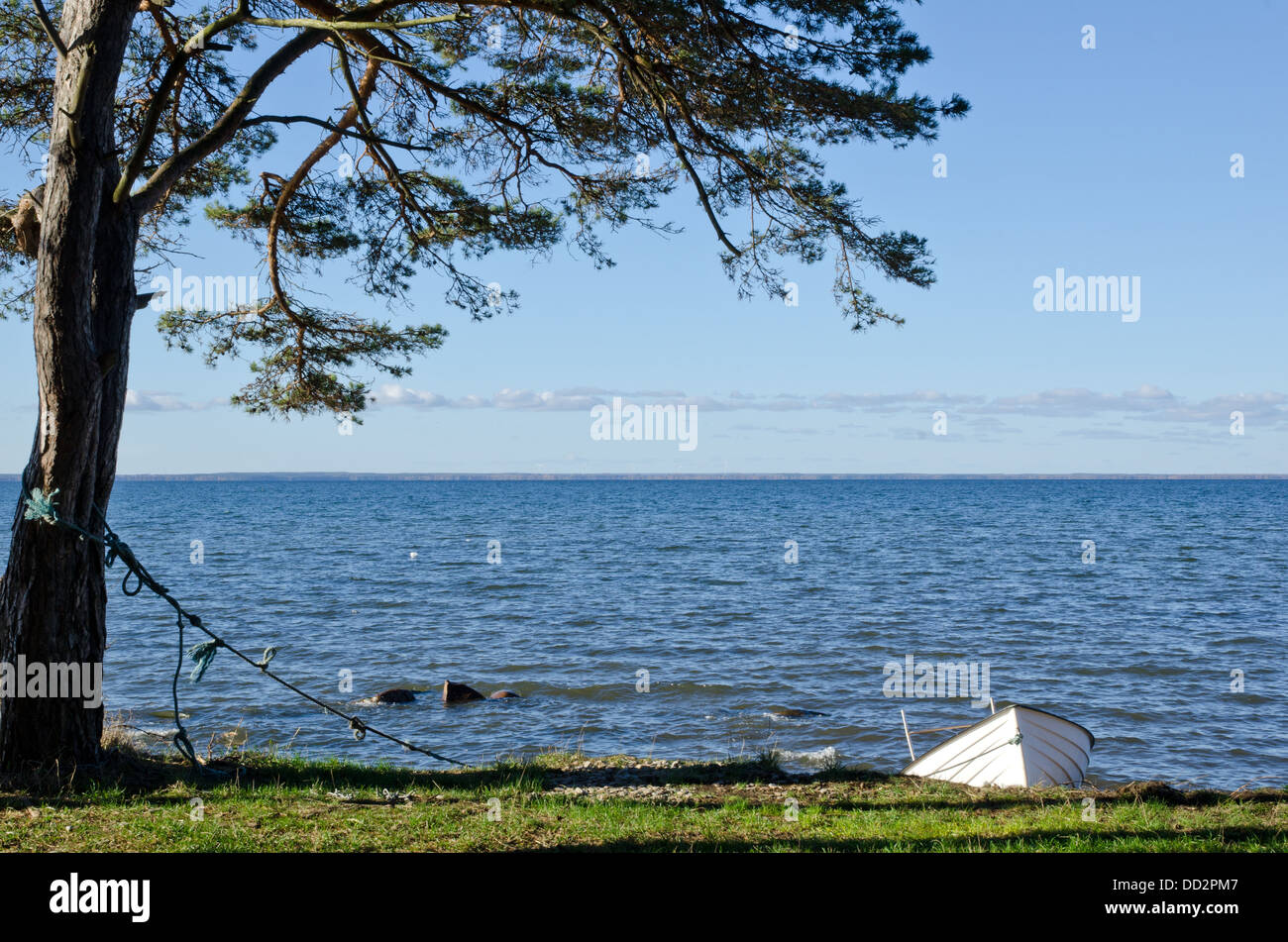 White rowing boat tied up at coast - Stock Image