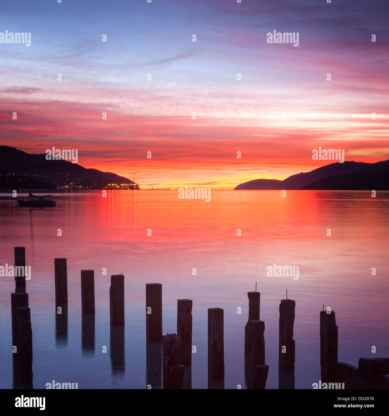 Beautiful sunrise with colours of red, orange and purple, over Governors Bay, Canterbury New Zealand. In the foreground - Stock Image