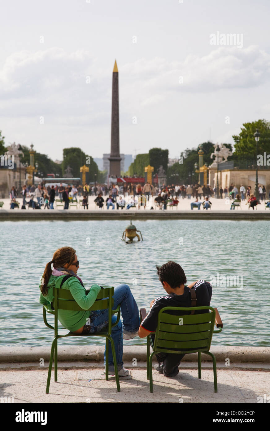 A couple sit in Jardin des Tuileries in front of Luxor Obelisk, Paris, France - Stock Image