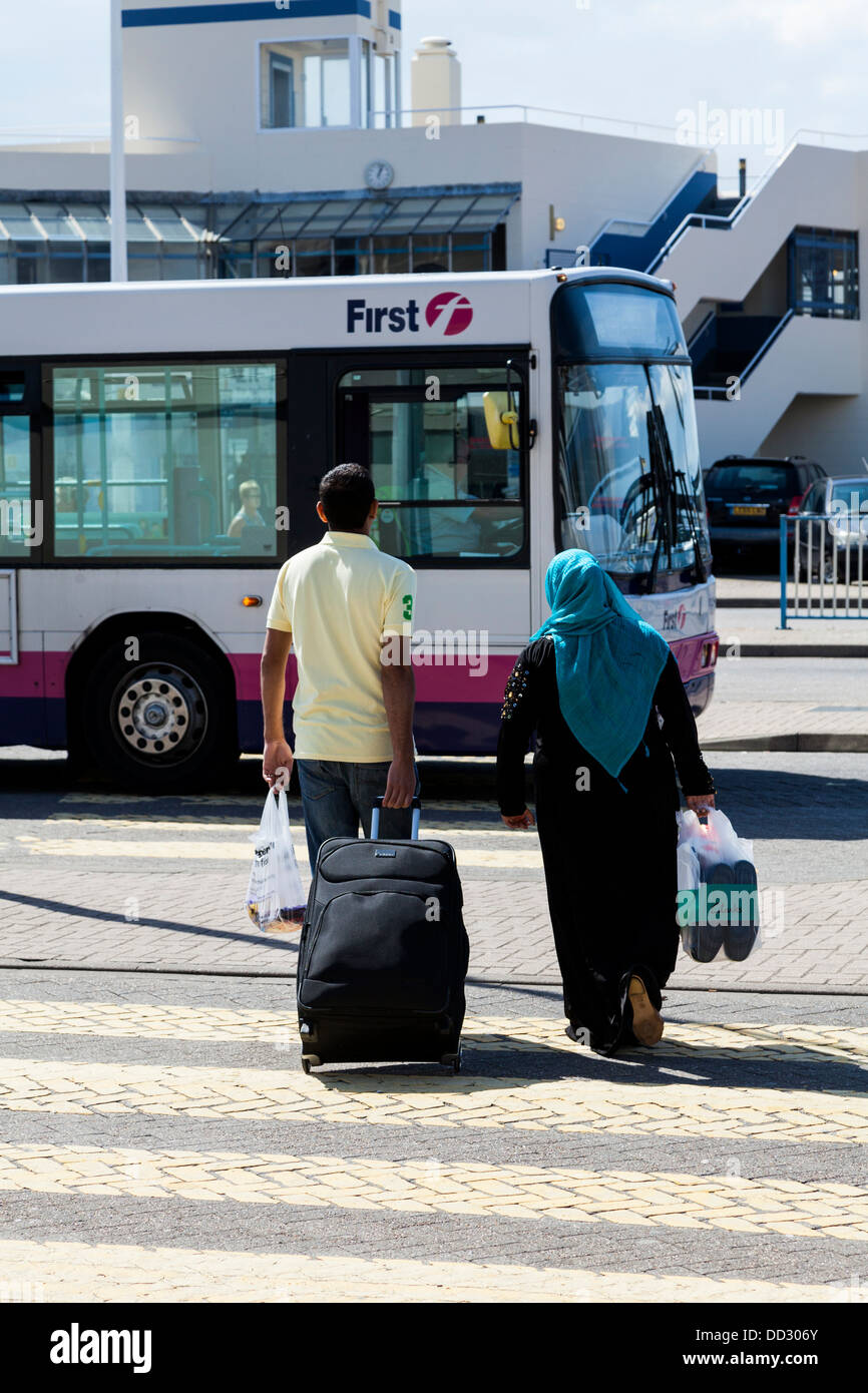 Two people, one in Burka, walking towards a bus, Portsmouth, Hampshire, England - Stock Image