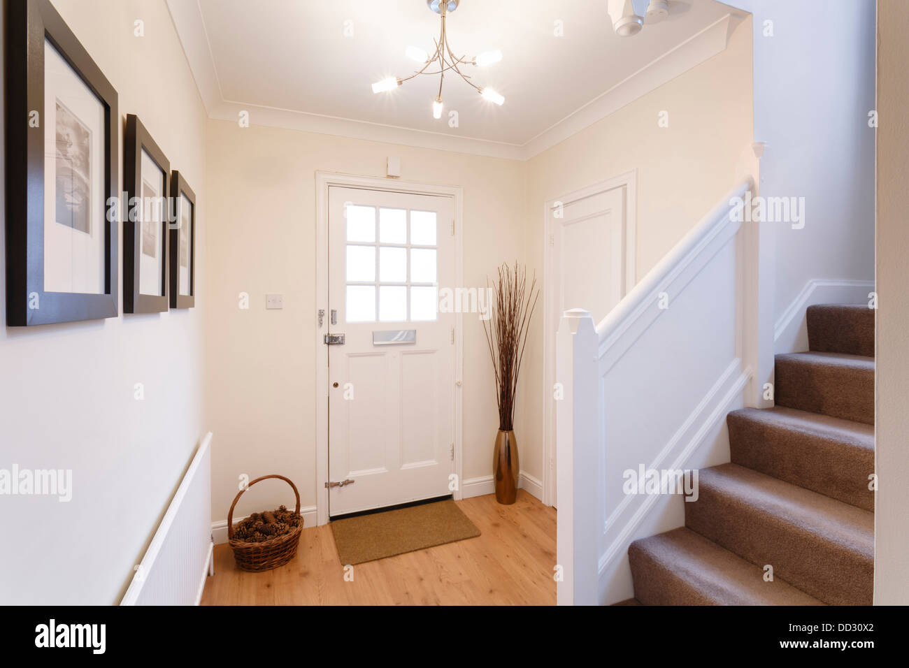 Home interior showing hallway and carpeted stairs - Stock Image