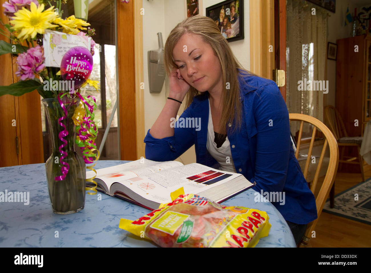 Young female student at kitchen table doing homework. Lindsborg, Kansas. - Stock Image