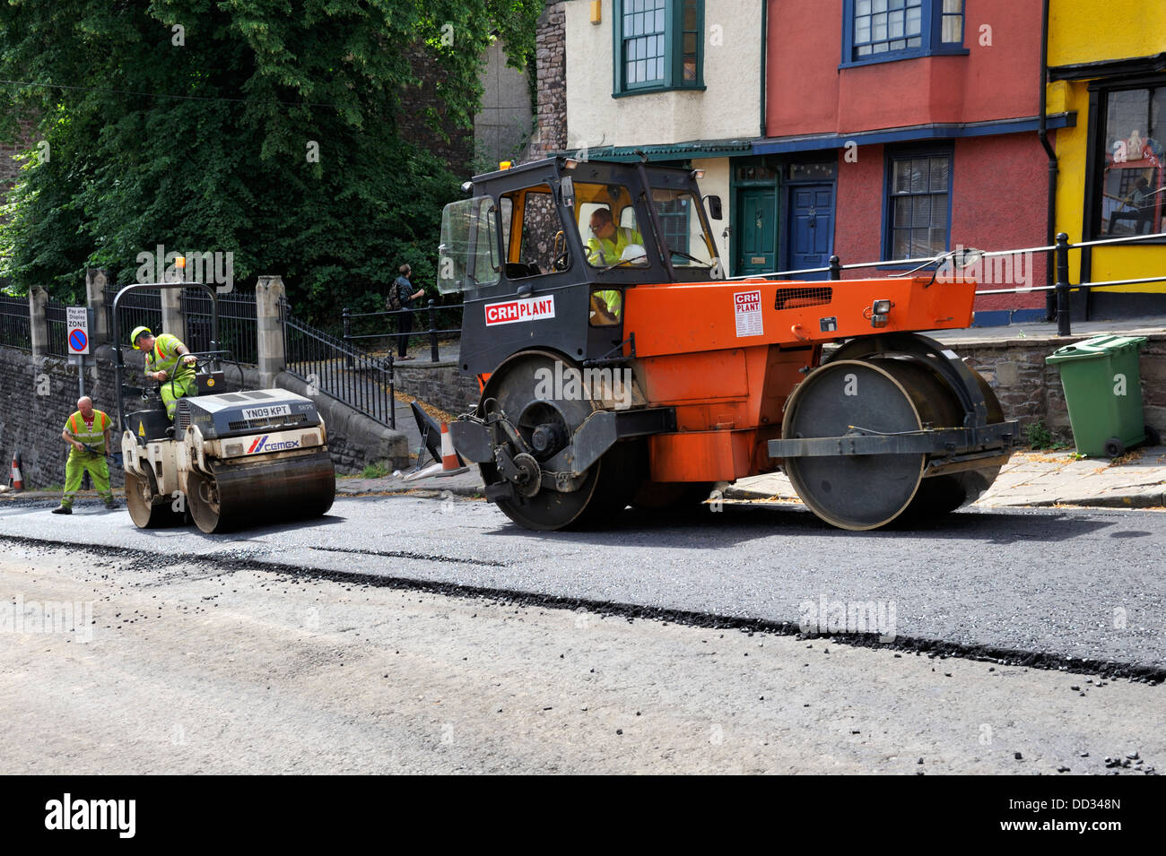 Large and small road rollers compacting asphalt during road resurfacing - Stock Image