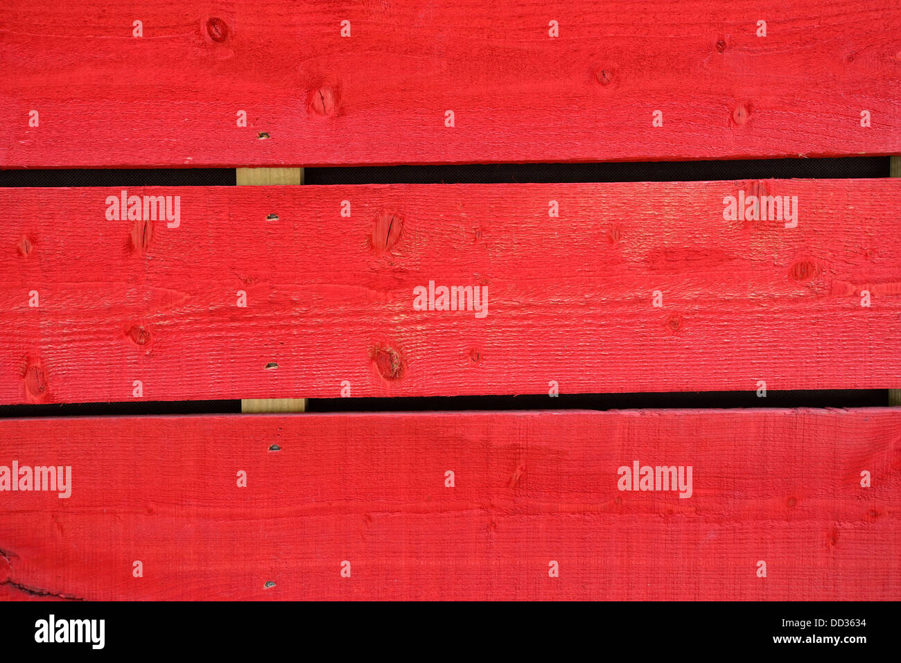 Planks of wood coloured in red - Stock Image
