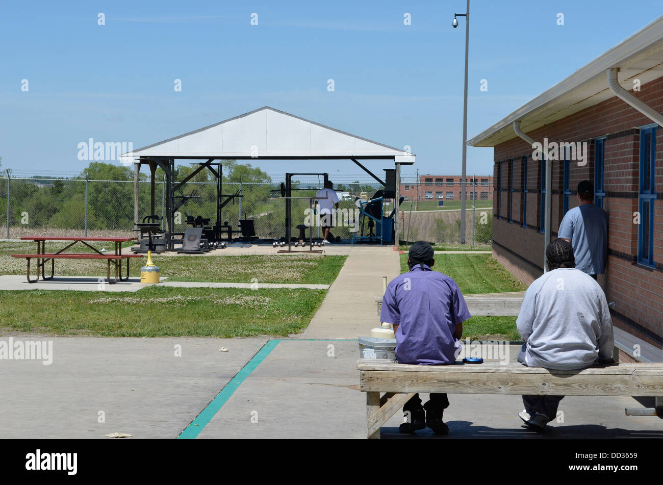 Inmates at work release prison sitting outside and working out. Lincoln Community Correctional Center. - Stock Image