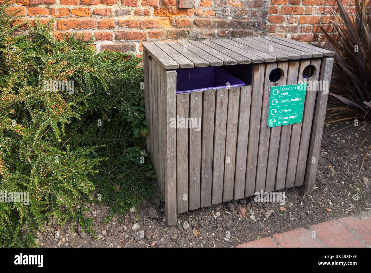 A wooden recycle bin in a park for recycling tins bottles cartons paper and card - Stock Image