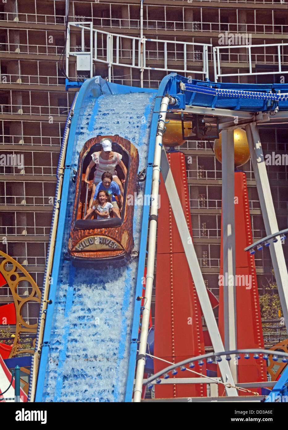 With apartment houses in the background a family rides the Wild River attraction at Luna Park in Coney Island, Brooklyn - Stock Image