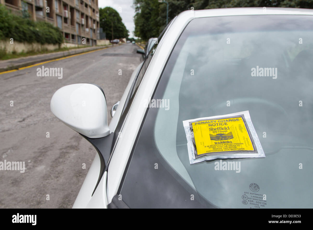 Parking ticket attached to illegally parked car on quiet street in Sheffield, South Yorkshire - Stock Image