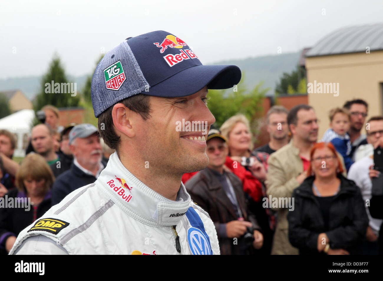 French rally driver Sebastien Ogier walks past spectators after the 15th special stage of the ADAC German Rally - Stock Image